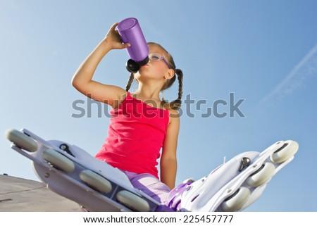 girl wearing roller skates sitting  - stock photo