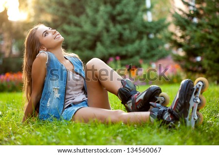 girl wearing roller skates sitting on grass in the park - stock photo