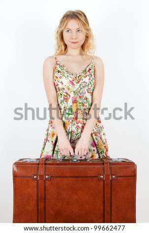 Girl wearing summer dress holds a vintage suitcase, anticipating travel. - stock photo