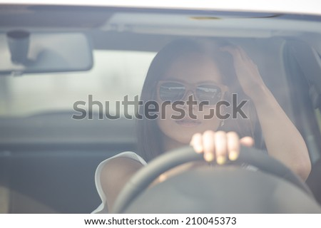 Girl wearing sunglasses driving white car - stock photo