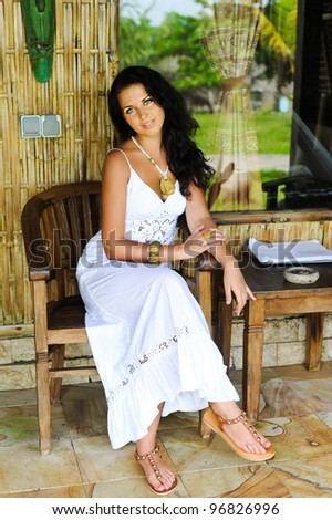 Girl wearing white dress sitting in the chair in  bungalow - stock photo