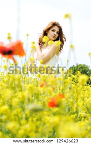 girl wearing white dress standing in the field - stock photo