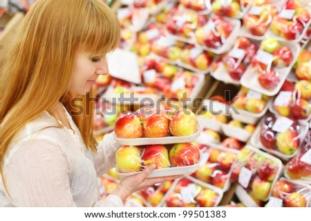 Girl wearing white shirt looks at packed apples in store; shallow depth of field - stock photo