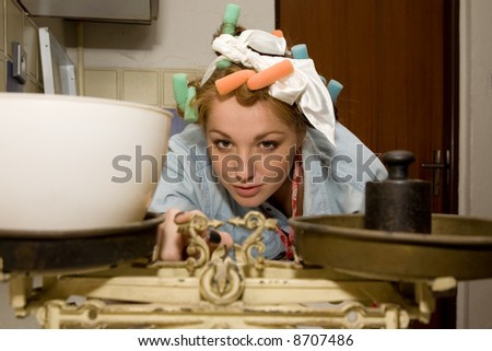 Girl weighting  food with hair curlers. - stock photo