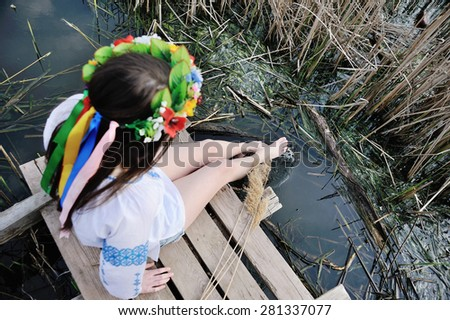 girl wets feet in the river. girl sitting on the bridge in the Ukrainian shirt and a wreath of flowers and ribbons on the head - stock photo