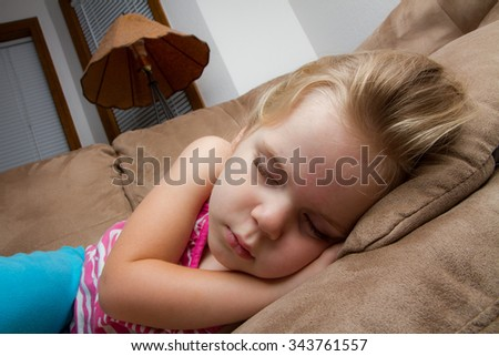Girl who fell asleep on the couch at night time - stock photo