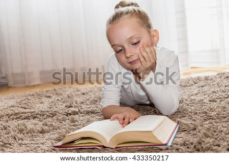 Girl who reads a book on living room floor - stock photo