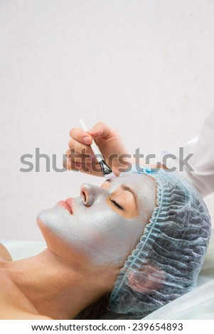 Girl with a beautician at spa salon. Beautician performs cosmetic procedures.applying cosmetic cream. Cosmetology, facial, beauty - The concept of facial skin care. Article about cosmetology. - stock photo