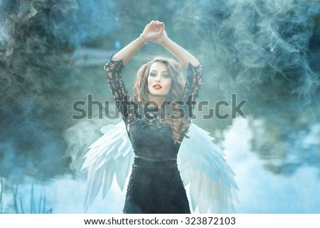 Girl with a beautiful face is to smoke. Behind her angel wings. - stock photo