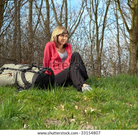 Girl with a big backpack sitting in a forest. - stock photo