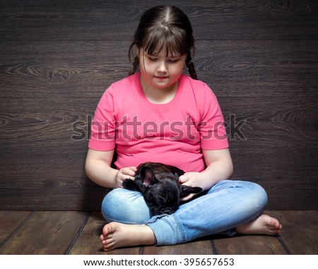 Girl with a black dog on the floor near the wooden walls. The dog - french bulldog puppy. Girl in jeans, barefoot. Dog and little mistress. Girl full - stock photo
