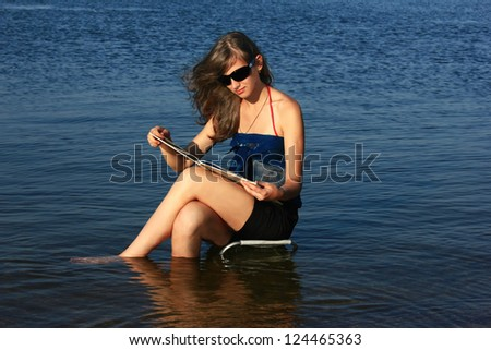 Girl with a book on the beach - stock photo