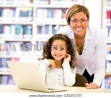 Girl with a computers teacher looking very happy - stock photo