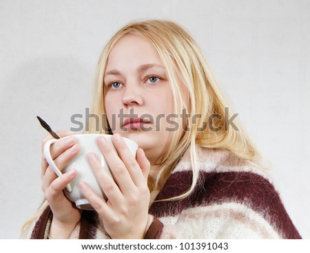 girl with a cup wrapped in a blanket. white background - stock photo