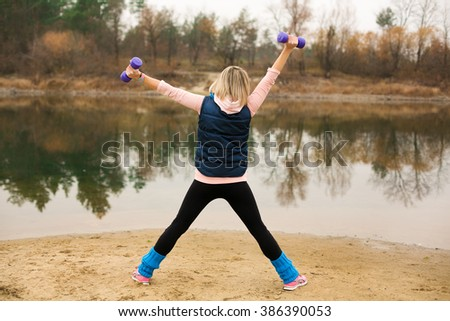 girl with a dog goes in for sports on the lake - stock photo
