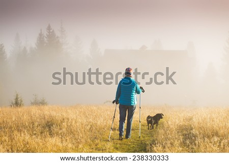 Girl with a dog goes towards the house standing on a mountain with Trekking pole in the morning fog. Landscape composition, background mountains and sunrise. - stock photo