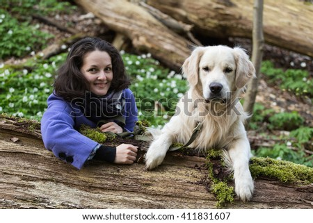 girl with a dog golden retriever look out from behind a tree - stock photo