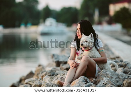 girl with a dog on the waterfront looking into the distance - stock photo