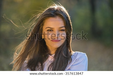 Girl with a fox expression on her face. Portrait of a beautiful sly looking teenage girl with brown eyes wearing pink shirt in the woods. Her hair floating in the wind. Warm autumn afternoon. - stock photo