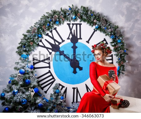 Girl with a gift and hairstyle sitting beside a large clock and a Christmas tree. Christmas Eve. New Year. Waiting for a miracle. 2017 - stock photo
