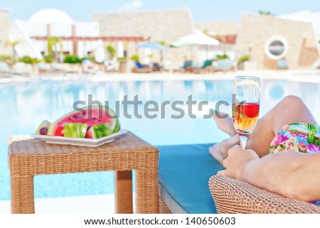 Girl with a glass of champagne and snacks watermelon. Against the background of the pool. - stock photo