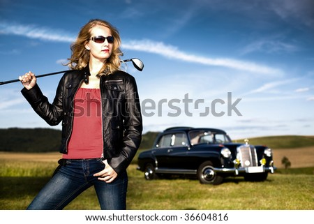 Girl with a golf driver and Post-War car Y.O.M. 1959 - stock photo