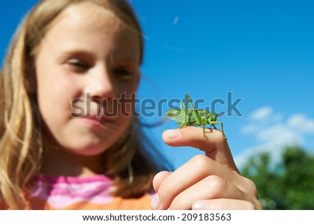 Girl with a grasshopper on a hand in summer - stock photo