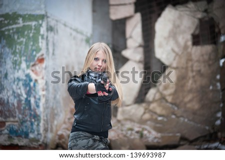 Girl with a gun in a ruined building - stock photo