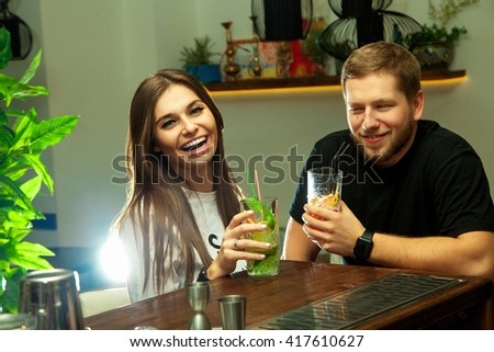 Girl with a guy at the bar laughing and drinking alcoholic cocktails - stock photo