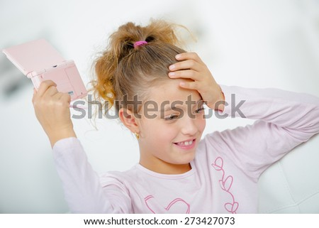 Girl with a hand held games console - stock photo