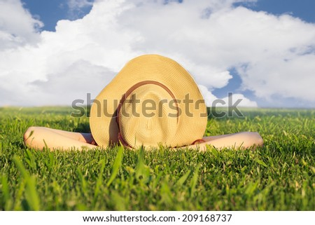 Girl with a hat, lying in the grass, enjoying sunny summer day. No visible face - stock photo