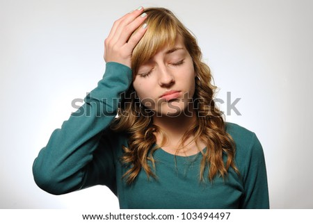 Girl With a Headache. Teenage girl with her hand on her head as if she has a headache. Note: not isolated. - stock photo