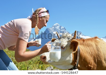 Girl with a jug of milk and a cow. Jungfrau region, Switzerland - stock photo