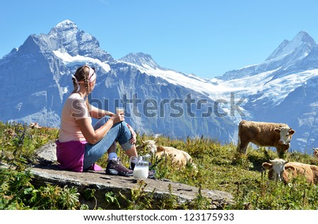 Girl with a jug of milk and cows. Jungfrau region, Switzerland - stock photo