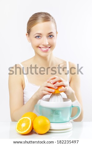 Girl with a juicer and oranges on a gray background - stock photo