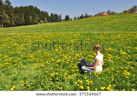 Girl with a laptop on the meadow - stock photo