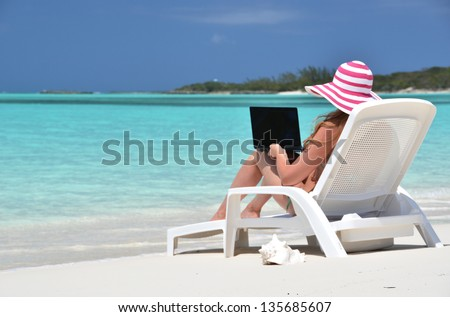 Girl with a laptop on the tropical beach. Exuma, Bahamas - stock photo