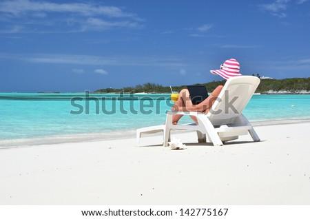 Girl with a laptop on the tropical beach. Exuma, Bahamas - stock photo