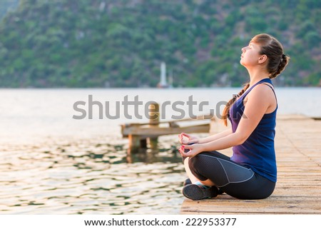girl with a long braid relaxes in a lotus position on the pier - stock photo