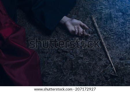 Girl with a magic wand lying on the ground - stock photo