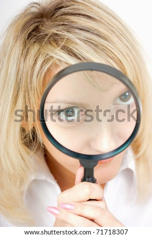 girl with a magnifying glass on a light background - stock photo