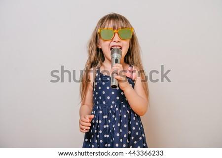 Girl with a microphone. little girl with a microphone. cute little girl singing with a microphone. karaoke. girl sings joyfully. girl singer. the little singer. - stock photo