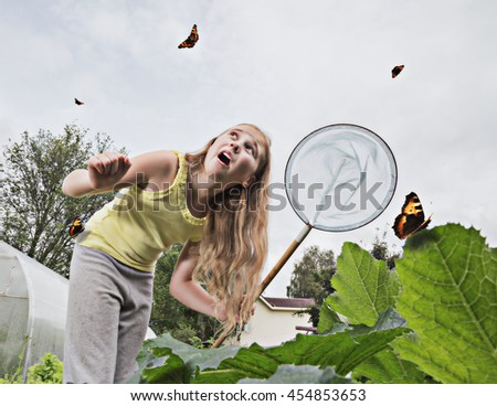 Girl with a net trying to catch butterflies. - stock photo
