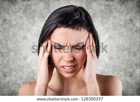 Girl with a painful head on a grey background - stock photo