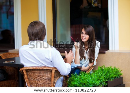 girl with a pen and pad and the guy sitting behind in a summer cafe - stock photo
