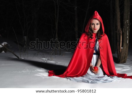 Girl with a red cloak sitting in the snow at night - stock photo