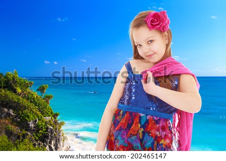 girl with a red scarf and a red bow on a background of blue sea.holiday at the seaside,active lifestyle,happiness concept,carefree childhood concept. - stock photo