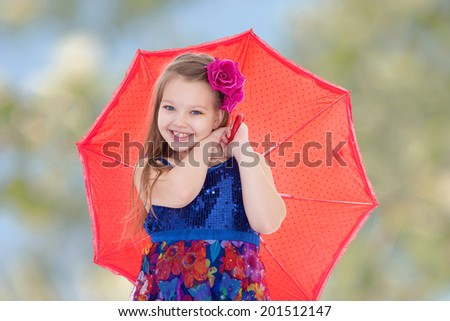 Girl with a red umbrella on the abstract background.spring season,fun outdoors,happy childhood,sweet child having fun outdoor,smiling toddler portrait - stock photo