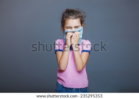 girl with a runny nose pressed her handkerchief to her nose - stock photo