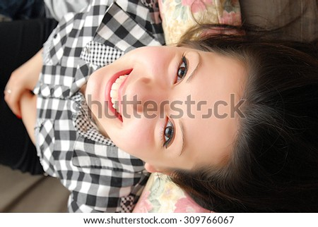 Girl with a smile on her bed - stock photo